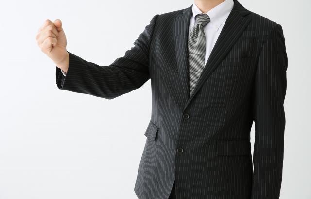 ガッツポーズするスーツの男性